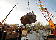 © Licensed to London News Pictures. 20/12/2011, Windsor, UK. The screw is lifted from a floating barge. One of the two giant 40 tonne Archimedes screws is lifted into place at Romney Weir on the River Thames. The screws, the largest in the UK and fish friendly, will generate 300 kilowatts of energy every hour to power Windsor Castle. It is the largest hydropower scheme in the South East of England. Photo credit: Stephen Simpson/LNP