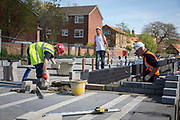 A group of builders use trowels to lay the first bricks with cement onto the foundations on new house construction site in Norwich. Norfolk. United Kingdom (photo by Andrew Aitchison / In pictures via Getty Images)
