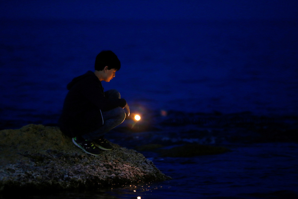 A boy places a candles on the shoreline rocks during a vigil to commemorate migrants who died at sea in Sliema, outside Valletta, April 22, 2015. European Union leaders who decided last year to halt the rescue of migrants trying to cross the Mediterranean will reverse their decision on Thursday at a summit hastily convened after nearly 2,000 people died at sea.  Public outrage over the deaths peaked this week after up to 900 migrants died last Sunday when their boat sank on its way to Europe from Libya. <br /> REUTERS/Darrin Zammit Lupi MALTA OUT. NO COMMERCIAL OR EDITORIAL SALES IN MALTA