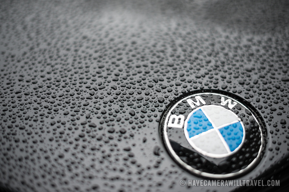 Close-up shot of a BMW badge on the hood of a black BMW car, with water droplets forming from rain. Shallow depth of field.