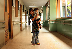 Haram Naz, 7, holds her 9-month-old sibling, Mezab Rahmat, in the hallway of the Children's Hospital at the Pakistan Institute of Medical Sciences, P.I.M.S., in Islamabad, Pakistan on Sept. 19, 2007. Their brother was being treated for typhoid fever.
