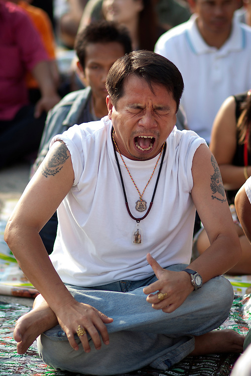 A devotee in deep trance scream during Sak Yant religious festival at Bang Phra Buddhist temple on Saturday, March. 03, 2012 in Nakhon Chaisi, Thailand. Thais come from all over Thailand to be tattooed by the temple's monks on their bodies being inked by hand using a long metal stylus. The religious tattoos are believed to be protection from ghost and bad spirits...