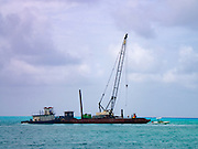 A crane on a floating platform, being held in position by a tug. The crew was lowering new channel markers into place.