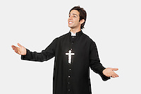 Young man in priest costume gesturing against gray background