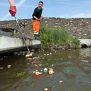 Nederland Den Haag 13 mei 2009 20090513 Foto: David rozing .Nieuwbouwwijk Wateringse Veld, medewerkers schoonmaak dienst vissen afval uit het water. opruimen,. opruimdienst, net, netten, visnet, schone omgeving, woonomgeving, sloot, watergang,   Foto: David Rozing