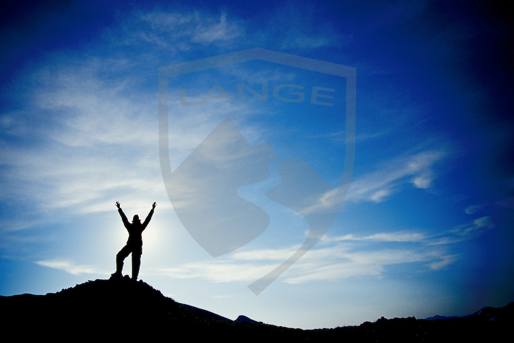 nature scenery and inspiring people concepts: colorado hiker silhouette with arms raised into big blue sky with clouds, devil's garden, pikes peak, rocky mountains, colorado, horizontal, copy space