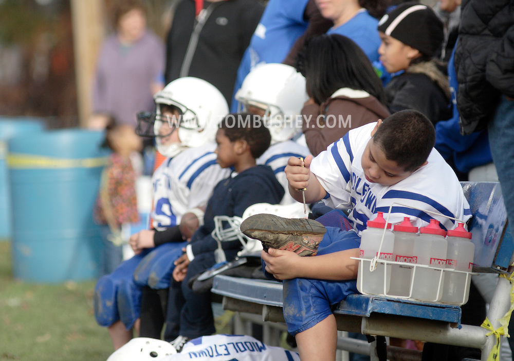Middletown, NY - A players uses a screwdriver to remove mud from his shoe while sitting on the bench during an Orange County Youth Football League Division 1 game on Nov. 14, 2009.
