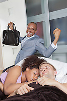 Multi-ethnic couple in bed with excited businessmen in background