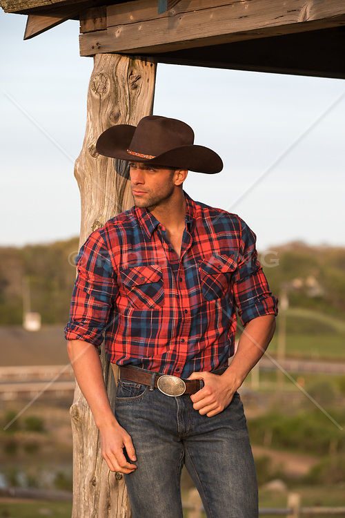 hot rugged cowboy leaning against a cabin