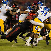 21 October 2016: The San Diego State Aztecs football team takes on the San Jose State Spartans Friday night at Qualcomm Stadium. San Diego State defensive lineman Sergio Phillips (65) brings down San Jose State running back Zamore Ziegler (34) in the second quarter. The Aztecs lead the Spartans 21-3 at halftime. www.sdsuaztecphotos.com
