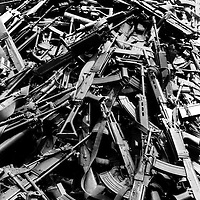 Gisenyi, Rwanda border, July  20th 1994, a pile of arms taken off the fleeing killers as they crossed into Zaire . There are guns from the  Hutu soldiers , but also a mass of machetes, knives, pounders , and assorted agricultural implements used by ordinary villagers to kill their ordinary neighbours .