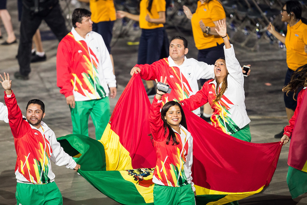Members of the Bolivian team wave to the crowd during the opening ceremonies at the Pan American Games in Toronto, Canada, July 10,  2015.  AFP PHOTO/GEOFF ROBINS