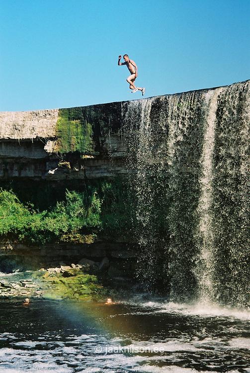 Teenage Boy Jumping Into Water From Jägala Waterfall Cliff, Harju County, Estonia