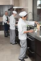 Three chefs work together in busy kitchen