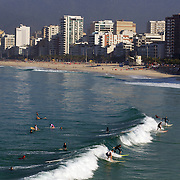 Early morning surfers at Ipanema beach catch a wave as the sunrise catches the light of the surrounding beachfront properties. Ipanema beach, Rio de Janeiro, Brazil. 9th July 2010. Photo Tim Clayton...The beaches of Rio de Janeiro, provide the ultimate playground for locals and tourists alike. Beach activity is in abundance as beach volley ball, football and a hybrid of the two, foot volley, are played day and night along the length and breadth of Rio's beaches. .Volleyball nets and football posts stretch along the cities coastline and are a hive of activity particularly at it's most famous beaches Copacabana and Ipanema. .The warm waters of the Atlantic Ocean provide the ideal conditions for a variety of water sports. Walkways along the edge of the beaches along with exercise stations and cycleways encourage sporting activity, even an outdoor gym is available at the Parque Do Arpoador overlooking the ocean. .On Sunday's the main roads along the beaches of Copacabana, Leblon and Ipanema are closed to traffic bringing out thousands of people of all ages to walk, run, jog, ride, skateboard and cycle more than 10 km of beachside roadway. .This sports mad city is about to become a worldwide sporting focus as they play host to the world's biggest sporting events with Brazil hosting the next Fifa World Cup in 2014 and Rio de Janeiro hosting the Olympic Games in 2016...
