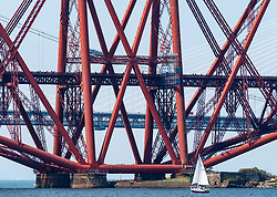Sailing boat beside Forth Bridge (Forth Railway Bridge) crossing the Firth of Forth between North and South Queensferry,UK