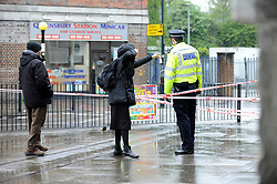 © Licensed to London News Pictures. 02/05/2018. LONDON, UK.  A police cordon surrounds the scene of a shooting in Queensbury, north west London.  A man was fatally shot and another injured following the shooting in Cumberland Road adjacent to Queenbury tube station.  It is reported that one of the victims staggered into a minicab office (pictured).  Photo credit: Stephen Chung/LNP