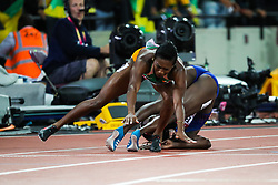 London, 2017 August 06. Tori Bowie, USA, and Marie-Josée Ta-Lou, Cote D'ivoire, crash to the ground after Bowie's narrow victory in the women's 100m final on day three of the IAAF London 2017 world Championships at the London Stadium. © Paul Davey.