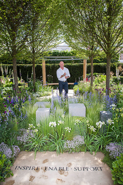 Actor Ross Kemp, on the Hope on the Horizon garden.  The<br /> &lsquo;Hope on the Horizon&rsquo; garden in aid of Help for Heroes: produced by building and landscaping firm Farr and Roberts&rsquo;, making their debut; designed by Matthew Keightley (29), as a result of his brother Michael&rsquo;s involvement with the armed forces, having served on four tours to Afghanistan and due for his fifth this year; and sponsored by the David Brownlow charitable foundation. The garden layout is based on the shape of the Military Cross, the medal awarded for extreme bravery. Granite blocks will represent the soldiers&rsquo; physical wellbeing and the planting represents their psychological wellbeing at various stages of their rehabilitation. Both evolve through the garden from a rough, unfinished, over-grown beginning through to a perfectly sawn, structured end. An avenue of hornbeams draws the attention through the entire garden to a sculpture resembling a hopeful horizon; a reminder to the soldiers that they all have a bright future ahead. As well as areas to recline and reflect, the garden offers focal points all the way through. Cool, calming colours are used throughout, helping to emphasise the fact that it will be a serene, contemplative space. After the Show, the garden will be moved and set within the grounds at Help for Heroes Recovery Centre at Chavasse VC House in Colchester, Essex. The garden will offer a serene, peaceful haven to contemplate and inspire a bright future and to support the challenging journey to recovery. The Chelsea Flower Show 2014. The Royal Hospital, Chelsea, London, UK.  19 May 2014.