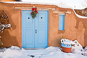 An aged blue wooden door with a bough of pine on an adobe style home in Taos, New Mexico.