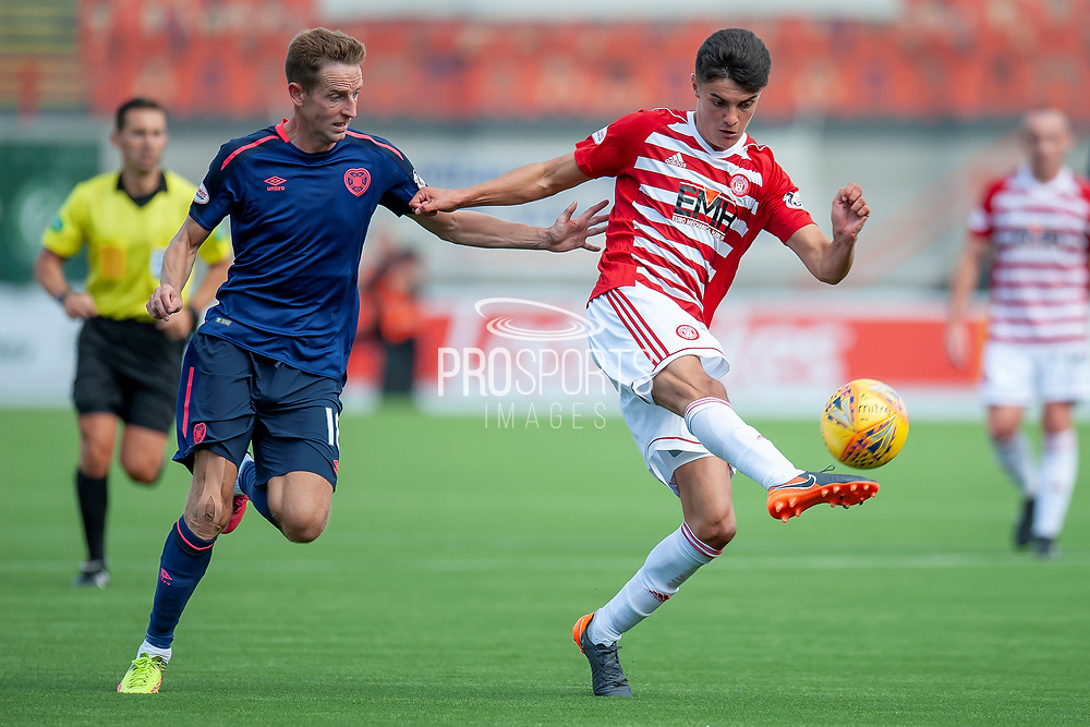 Alex Penny of Hamilton Academical FC clears the ball from Steven MacLean of Heart of Midlothian during the Ladbrokes Scottish Premiership League match between Hamilton Academical FC and Heart of Midlothian FC at New Douglas Park, Hamilton, Scotland on 4 August 2018. Picture by Malcolm Mackenzie.