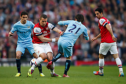 Arsenal Forward Lukas Podolski (GER) is challenged by Man City Midfielder David Silva (ESP) - Photo mandatory by-line: Rogan Thomson/JMP - 07966 386802 - 29/03/14 - SPORT - FOOTBALL - Emirates Stadium, London - Arsenal v Manchester City - Barclays Premier League.