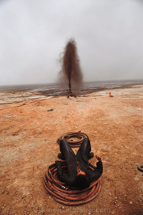 An exhausted Wild Well Control Inc. worker takes a break while capping an oil well after they extinguished the fire. The burning Al Burgan oil fields in Kuwait after the end of the Gulf War in May of 1991 were covered in oil that rained down from the clouds of oil smoke and oil shooting into the air after a fire had been extinguished. More than 700 wells were set ablaze by retreating Iraqi troops creating the largest man-made environmental disaster in history. Photo taken on July 8, 1991.