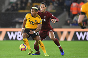 Liverpool defender Virgil van Dijk (4) holds up Wolverhampton Wanderers Forward Adama Traore (37) during the Premier League match between Wolverhampton Wanderers and Liverpool at Molineux, Wolverhampton, England on 21 December 2018.