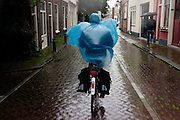 Fietsers rijden door de stromende regen door Utrecht.<br /> <br /> A woman is riding in the rain in Utrecht.