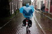Fietsers rijden door de stromende regen door Utrecht.<br /> <br /> A woman is riding in the rain in Utrecht.
