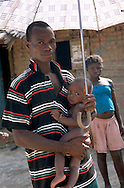 Young father with a baby in a remote village of southeast Cameroon.