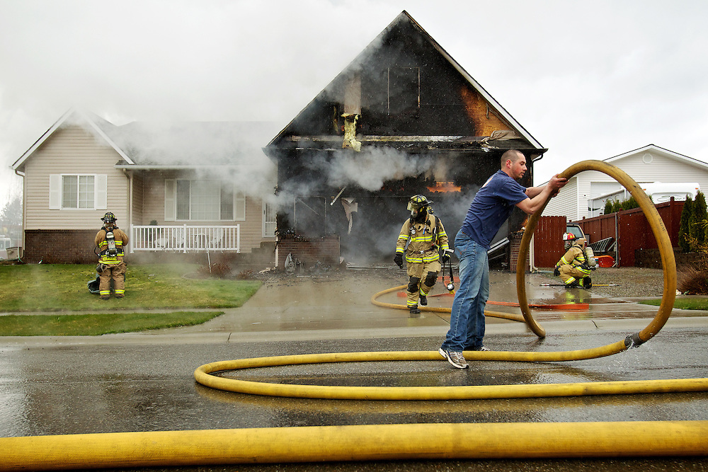 Kelan McKeirnan, an off-duty Coeur d'Alene firefighter, helps straighten a hose Tuesday as other firefighters from Coeur d'Alene and Kootenai County fire agencies orchestrate efforts to extinguish a garage fire at the 2000-block of Greenleaf Avenue in Coeur d'Alene. McKeirnan, who lives in the area, saw the smoke and flames from his house and helped on scene until rescue personnel arrived. There were no injuries reported in the fire which is still under investigation.
