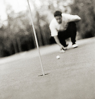 Man lining up golf putt (grainy, B&W)(focus on foreground)