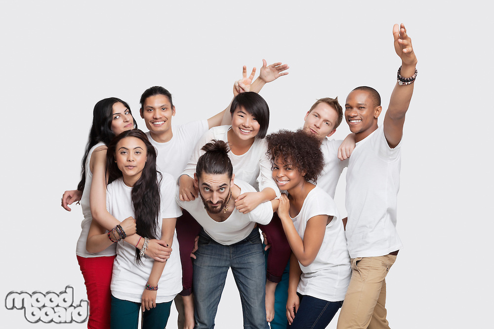 Portrait of cheerful young multi-ethnic friends posing against white background