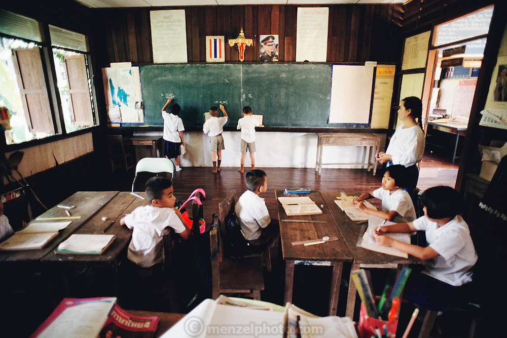 Nine-year-old Visith Khuenkaew, (at the blackboard on the right), and his fellow third grade classmates work on math problems at school near their village of Ban Muang Wa, Thailand. The Khuenkaew family lives in a wooden 728-square-foot house on stilts, surrounded by rice fields in the Ban Muang Wa village, outside the northern town of Chiang Mai, in Thailand. Material World Project.