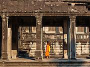 Buddhist monk in orange robe at Angkor temple (Cambodia)
