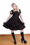Model wearing lolita style dress with high heeled boots on white background