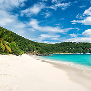 A beautiful sandy beach at White Bay on Jost Van Dyke in the British Virgin Islands in the Caribbean. The beach is famous for a string of bars serving tropical drinks, most famously the Soggy Dollar Bar.