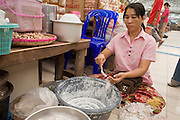 "24 FEBRUARY 2008 -- MAE SOT, TAK, THAILAND: A Burmese woman packages home made tooth whitener in the Burmese market in Mae Sot, Thailand. There are millions of Burmese refugees living in Thailand. Many live in refugee camps along the Thai-Burma (Myanmar) border, but most live in Thailand as illegal immigrants. They don't have papers and can not live, work or travel in Thailand but they do so ""under the radar"" by either avoiding Thai officials or paying bribes to stay in the country. Most have fled political persecution in Burma but many are simply in search of a better life and greater economic opportunity.  Photo by Jack Kurtz"