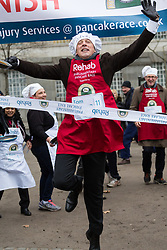 MPs and members of the House of Lords compete in the annual Rehab pancake race, a relay of eleven laps in Victoria Tower Gardens adjacent to the Houses of Parliament in London. The race is held every year on Shrove Tuesday and was won by the Media team. PICTURED: Tom Newton Dunn of The Sun wins it for the media team. London, February 13 2018.