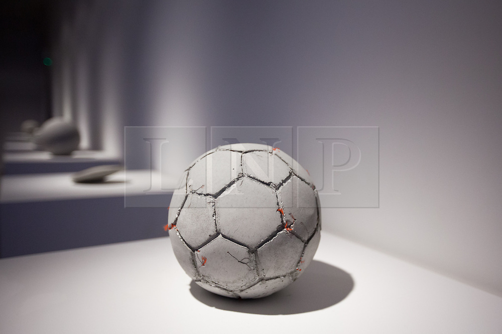 © Licensed to London News Pictures. 20/06/2013. London, UK. 'Football' (2012) a sculpture made using reconstituted concrete from the West Bank-Israel 'apartheid wall' is seen with other pieces by Palestinian artist Khaled Jarrar at the press view for a new exhibition at the Ayyam Gallery in London today (20/06/2013). The exhibition, entitled 'Whole in the Wall', uses cement taken by Khaled from the 700km long apartheid wall that separates the West Bank from the State of Israel. Photo credit: Matt Cetti-Roberts/LNP