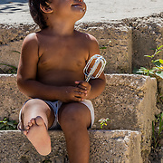 A young child enjoys licking the beater on the steps of their home in Santiago, Cuba.