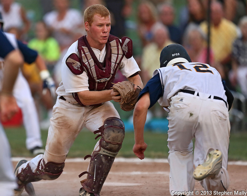 Mount Vernon catcher Conner Welch (7) tags out Iowa City Regina's Mark Ward (12) at the plate during the 2A District Finals game at West Branch High School in West Branch on Saturday, July 20, 2013.