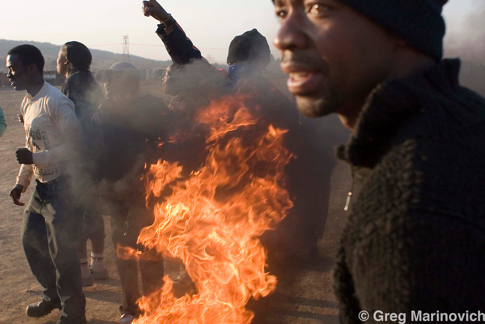 Residents of Boiketlong informal settlement burn tyres 1 sept 2007 2007.  Informal that dot the Sebokeng/Evation area south of Johannesburg have been taking to the streets to protest lack of service delivery, or inadequate services that are not what they believe were promised them by the African National Congress before they came into power in 1994.  Photo Greg Marinovich