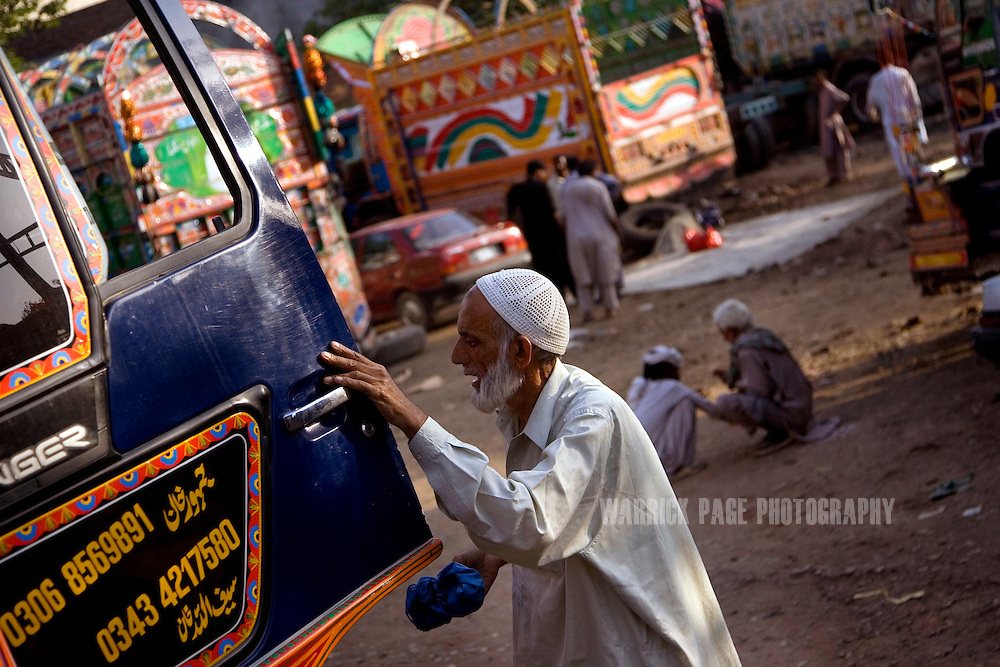 RAWALPINDI, PAKISTAN - OCTOBER 9: A Pakistani truck-artist closes the door on a recently completed vehicle at a painting and repair yard, October 9, 2008, in Rawalpindi, Pakistan. The heavily adorned Bedford trucks have become a national icon and cost upwards of one million rupees (USD$12,500) for a full makeover. Much of the artwork consists of a cultural mix of religious and secular, Pakistani film and music stars, cricket legends, romanticized military imagery of F-16 fighter jets and Ghauri missiles, the Prophet's winged horse, Buraq, and dreamlike scenes of wooded lakes and snow-capped mountains and exotic animals. (Photo by Warrick Page)