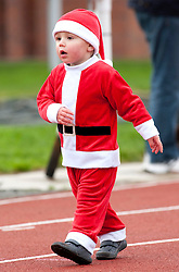 © Licensed to London News Pictures. 11/12/2011, Nuneaton, Warwickshire, UK. Over 200 people dressed in Santa outfits ran a mile to raise money for the Mary Evans Hospice appeal earl;ier today. The charity raised over four thousand pounds last year and organiser Janet Kavangah from the hospice said they were hoping to better that this year. Pictured, this young santa determined to complete the course. Photo credit : Dave Warren/LNP