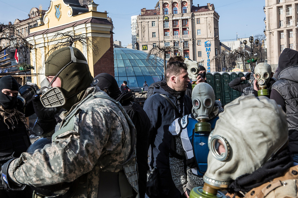 KIEV, UKRAINE - FEBRUARY 19: Anti-government protesters put on gas masks near the perimeter of Independence Square, known as Maidan, on February 19, 2014 in Kiev, Ukraine. After several weeks of calm, violence has again flared between police and anti-government protesters, who are calling for the ouster of President Viktor Yanukovych over corruption and an abandoned trade agreement with the European Union. (Photo by Brendan Hoffman/Getty Images) *** Local Caption ***