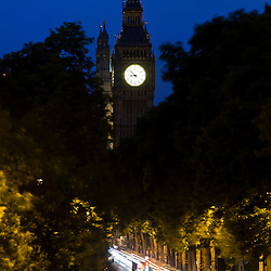 Traffic on Victoria Embankment in London, light streaks at dusk. Big Ben tower with English flag on the background.