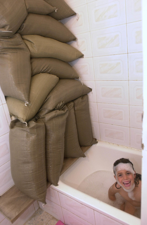 Rachel Jacobi, 5, plays peek a boo as she takes a bath before going to bed in her home's bathroom which has been sandbagged to protect the family from Palestinian fire comming in from the West Bank town of Ramallah in to the Jewish settlement of Psagot, Israel Monday Dec. 4, 2000.