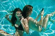 2 Teenage girls using mobile phones underwater in swimming pool